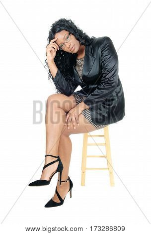 A beautiful African American business woman in a jacket heels and glasses sitting on a chair isolated for white background.