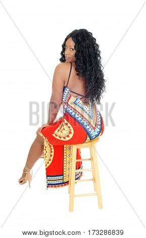 A beautiful young African American woman sitting in a colorful dress from the back isolated for white background.