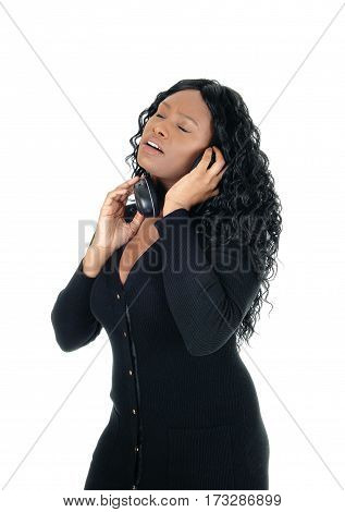 A young African American woman listening with her headphones to music with her eyes closed isolated for white background.
