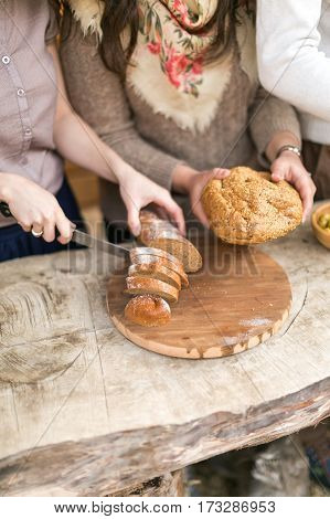 the woman cuts bread on a wooden board. top view.