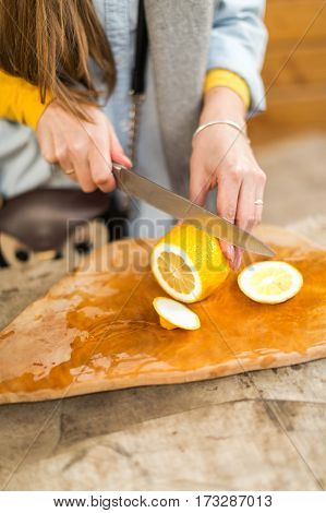 Woman cuts lemon on a wooden board