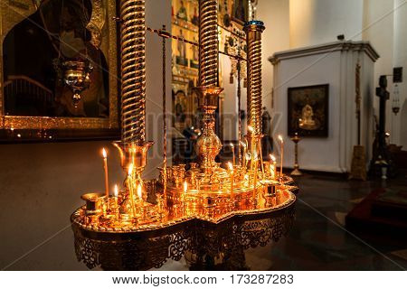 YAROSLAVL, RUSSIA - NOVEMBER 20, 2016: Interior view of Assumption Cathedral - decorated golden altar candle with lighted candles. Famous touristic place in Yaroslavl - Golden Ring tour in Russia