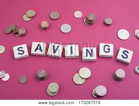 Text: Savings from wooden letters on a red office desk.