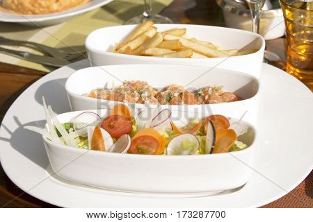 Fresh vegetables, salmon tartar, French fries on the table in a restaurant