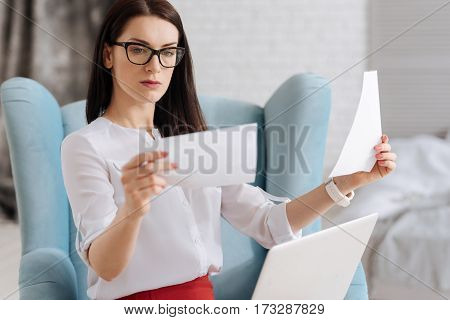 What is better. Beautiful thoughtful pleasant woman holding two pictures and comparing them while deciding which one is better