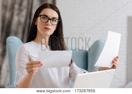 Need to choose one. Pleasant brunette young woman looking at the pictures and choosing which one is better while doing her job