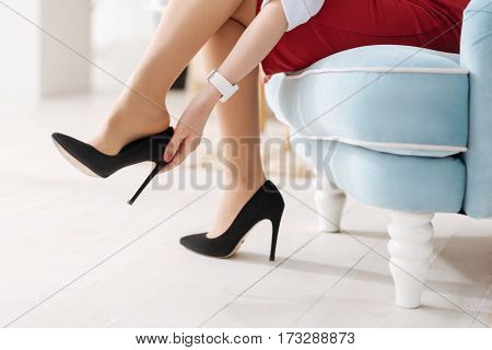 Coming home. Close up of elegant high heel shoes being taken off by a beautiful nice woman while coming home
