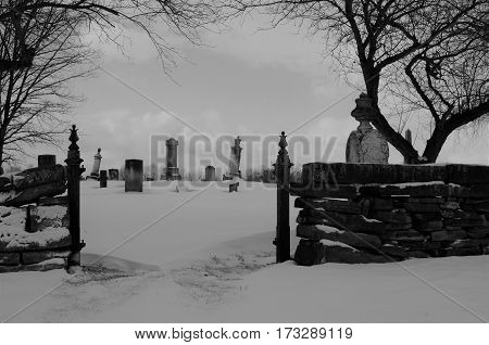 Entrance to old Amish cemetery in the country covered in snow in Black and white