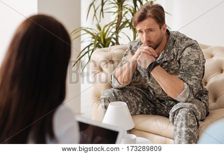 Professional advice. Depressed handsome nice man holding his chin and listening to his therapist while visiting a psychologist