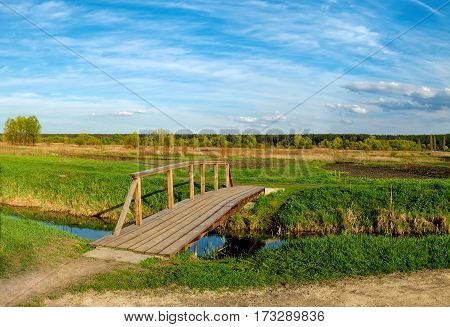 Road banks of a small river with wooden bridge over it agricultural fields and forest on the horizon, Irpin, Ukraine. Panorama of typical Ukrainian rural landscape in spring.