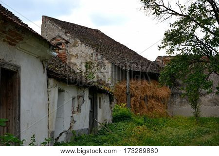 Courtyard of the fortified medieval saxon church in Ungra, a commune in Bra?ov County, Romania. Here there is a medieval 13th century Transylvanian Saxon church and many old houses poster