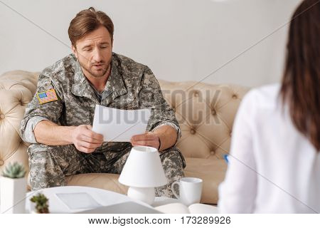 What do you see here. Nice handsome military man sitting on the sofa and holding a sheet of paper while undergoing psychological treatment