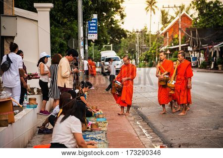 LUANG PRABANG, LAOS - JULY 27, 2016: Alms giving in the morning when monks walk by the streets for the food. Tourists with cameras and young monks in Luang Prabang, Laos