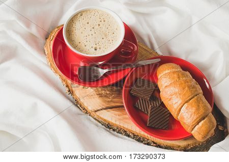 Breakfast in Bed Tray with Cappuccino Chocolate and Croissants on a Bed with Plaid in Bedroom Interior. Selective Focus.
