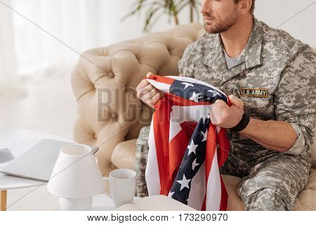 True patriot. Sad handsome bearded soldier sitting on the sofa and holding the US flag while thinking about his country