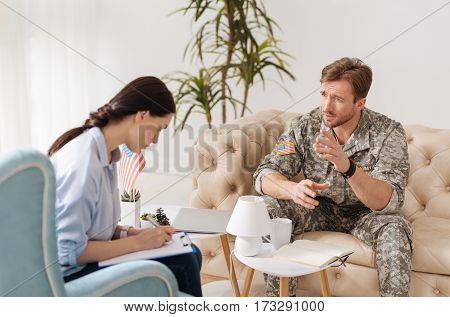 Discussing a problem. Nice handsome military man sitting on the sofa and talking to his therapist while discussing his problems