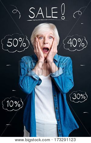 Big season sales. Pleasant emotional senior woman opening her mouth and holding her cheeks while being surprised about the sales