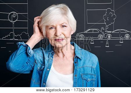Heavy traffic. Nice thoughtful elderly woman standing on the street and holding her head while looking at the car crash