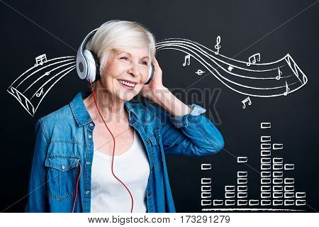 Wonderful mood. Positive delighted aged woman wearing headphones and smiling while listening to music