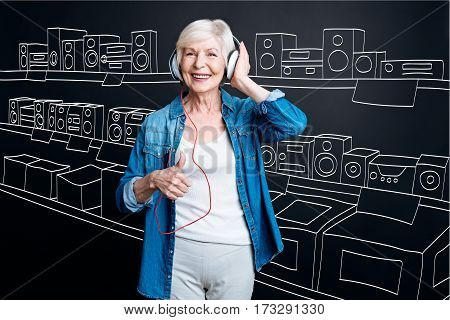 Music lover. Happy positive senior woman visiting the appliance store and enjoying the music in headphones while choosing a new stereo system