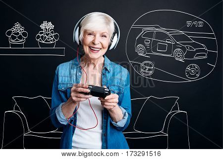 Car race. Joyful positive elderly woman holding a game console and wearing headphones while playing a car race