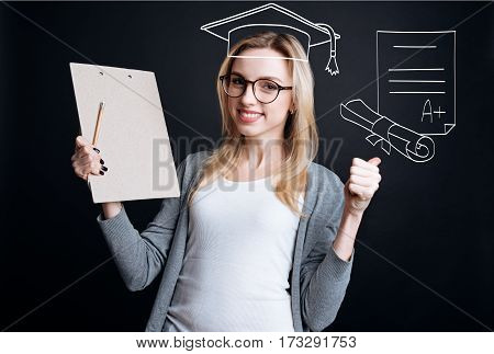 University graduation. Joyful smart female student holding her diploma and wearing an academic cap while graduating from the university