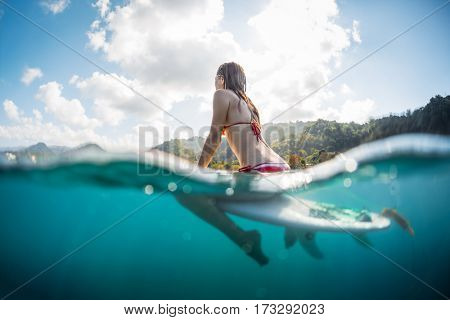 Young woman sits on the surfboard in the ocean, underwater splitted shot.