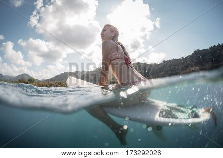 Young woman sitting on the surfboard with splitted underwater view