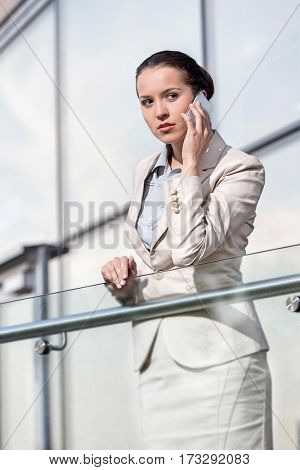 Beautiful young businesswoman using smart phone at office railing