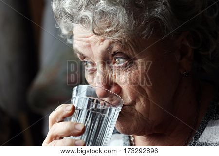 Grandmother drinks water on a dark background