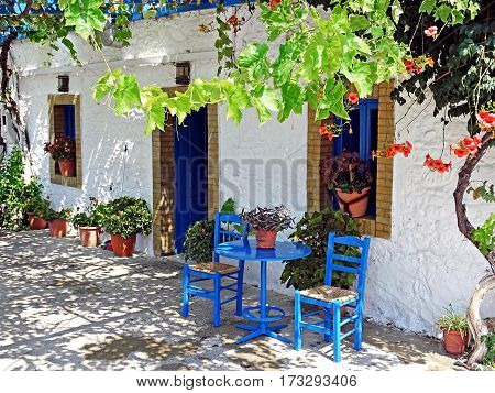 House in Kos with in the typical for Greece blue-painted furniture in front of it