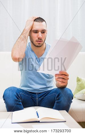 Young man looking at his document in panic while working at his home.
