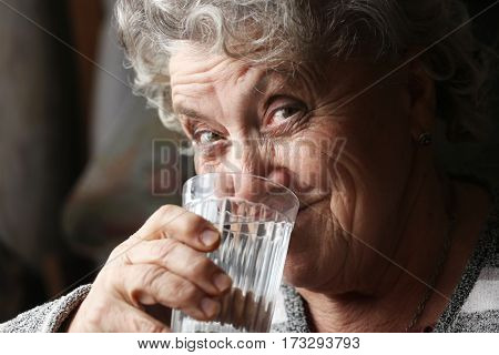 Smile grandmother drinks water on a dark background