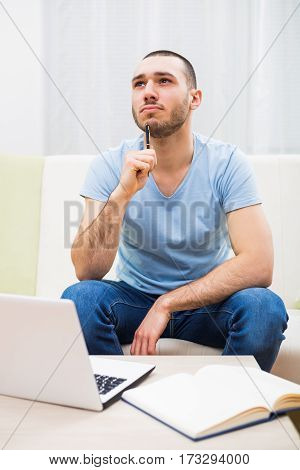 Young businessman thinking while using laptop and  working at home.