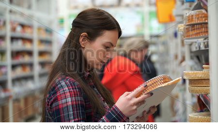 woman buys shortcakes in supermarket or store