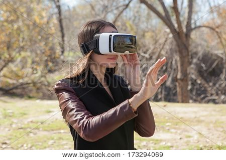 Young woman wearing virtual reality goggles, standing in a park