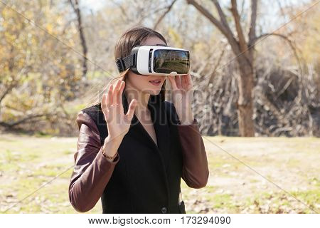 woman using modern virtual reality glasses outdoor