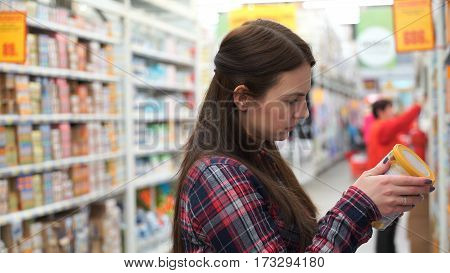 Young mom buys baby food in supermarket
