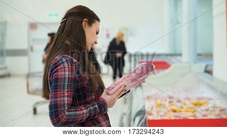 woman buys meat in supermarket or store