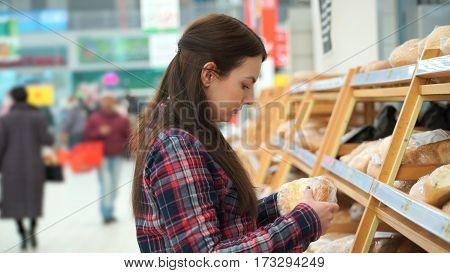 woman buys bread in supermarket or store