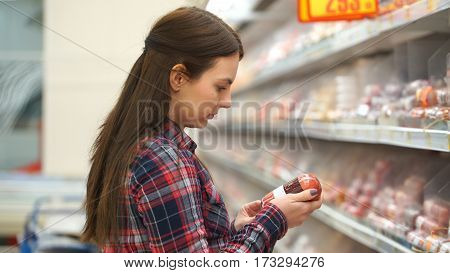 woman buys sausage in supermarket or store