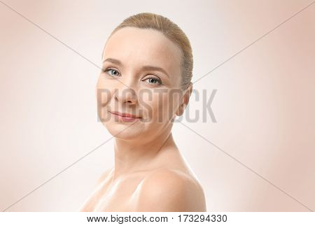 Mature woman on color background. Plastic surgery concept.