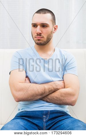 Photo of angry young man sitting at sofa.