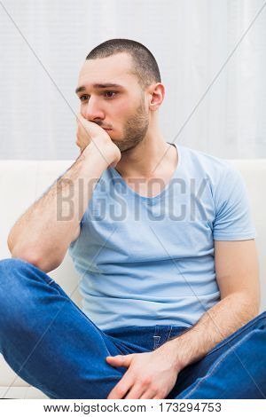 Depressed young man is sitting at the sofa and thinking about something.