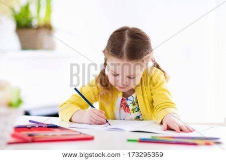 Cute little girl doing homework reading a book coloring pages writing and painting. Children paint. Kids draw. Preschooler with books at home. Preschoolers learn to write and read. Creative toddler poster