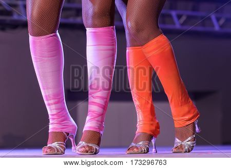 female legs of an attractive cabaret dancer in fishnet stockings. women's feet in shoes with heels. dancer legs Heeled sandals on dance floor.