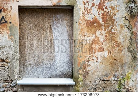 abandoned grunge cracked stucco wall with with boarded up window