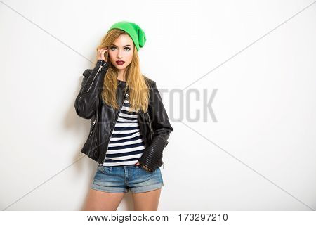 Street Style Hipster Girl Posing at White Background. Not Isolated Photo with Shadow and Copy Space. Young Female Model. Trendy Casual Fashion Outfit in Spring or Summer.