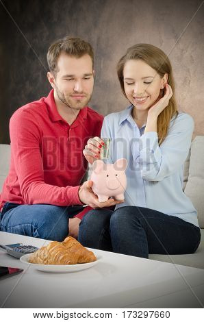 Young Couple Saves Into Piggybank