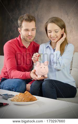 Young Couple Saves Into Piggybank